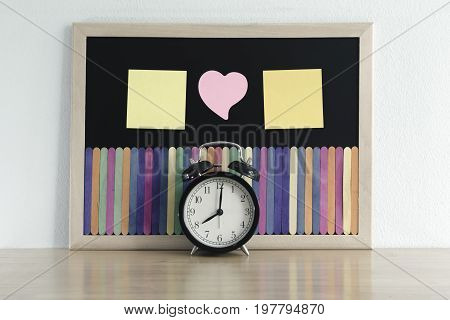 Retro alarm clock in front of Black board and beautiful color of ice cream stick with empty note paper for adding message. Back to school love and time management concept.