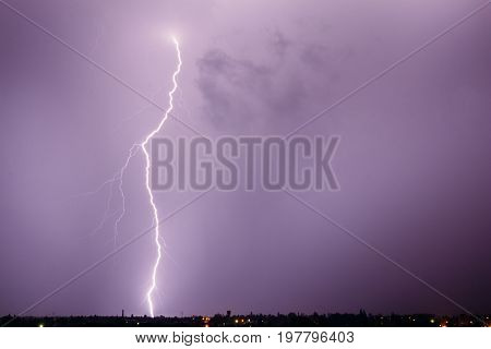 Lightning strikes from the storm sky right into the ground behind a small town. Nature and weather