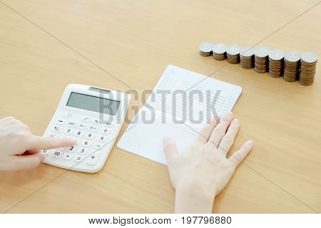 Businesswoman use calculator beside passbook and Coins