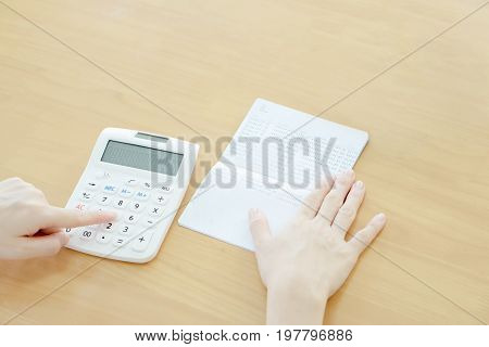 Businesswoman use calculator beside passbook, account, finance