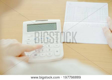 Blur businesswoman use calculator beside passbook, account