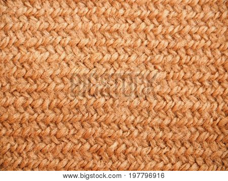 A full page of synthetic faux material. Macro brown sweater, knitted wool texture. View of top on background texture. Braided wool texture closeup