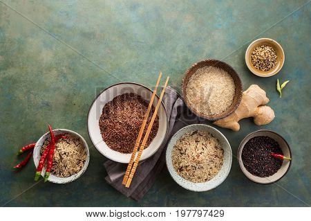 Assortment of different rice in bowls and spices: white rice, red rice, black rice, a mixture of wild and brown rice.