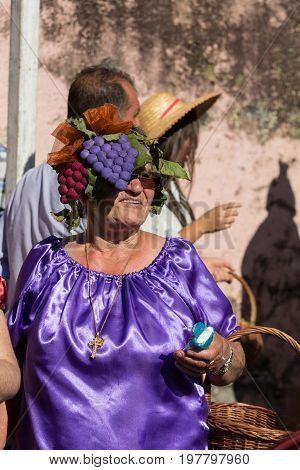ESTREITO DE CAMARA DE LOBOS PORTUGAL - SEPTEMBER 10 2016: Woman wearing in colorful costume at Madeira Wine Festival in Estreito de Camara de Lobos Madeira Portugal. The Madeira Wine Festival honors the grape harvest with a celebration of traditional loca