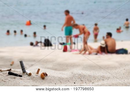 Cigarette butts ashtray on the beach with a lot of tourists by the sea.