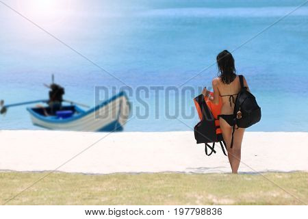 Tourist girl with luggage on the beach and long tail boat in the sea.Samui island Thailand.