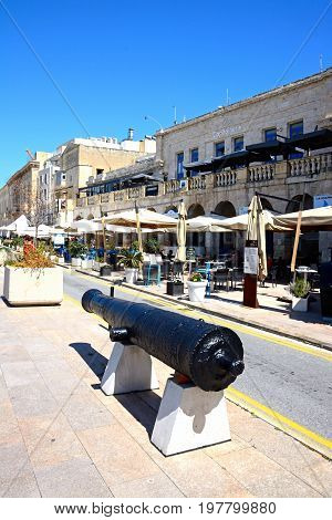 VITTORIOSA, MALTA - MARCH 31, 2017 - Cannon along the waterfront with pavement cafes to the rear Vittoriosa (Birgu) Malta Europe, March 31, 2017.