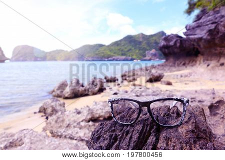 Damaged sunglasses on the rocks on the beach at Angthong Island Thailand.