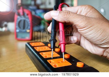Electricians worker use voltmeter measure the current from extension cord sets plug.