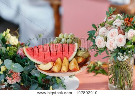 The banquet table with fruits. Watermelon and peaches