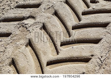 Tire tread footprints of a tractor on the sand.