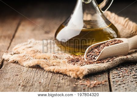 flax seeds and linseed oil in a glass jug on a wooden table, healthy diet with omega 3 fatty acids