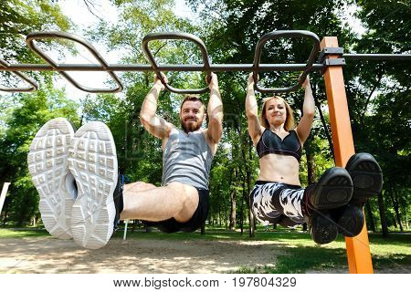 Young sportive woman and bearded man doing pull-ups exercises on crossbar in a parrk at summer day. Wide angle shot/