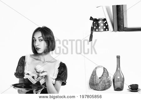 woman housemaid with attractive serious face in servant uniform holding plate with apple posing in kitchen isolated on white black and white