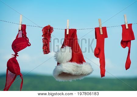 New year costume on blue sky. Laundry and dry cleaning. santa clothes for drying. Xmas red costume on rope with pin. Christmas clothes outdoor.