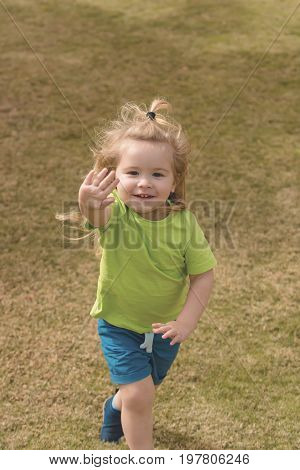 Boy little child blond with happy smiling adorable face in green shirt and gray short running having fun and waving his hand on background of natural grass at summer sunny day