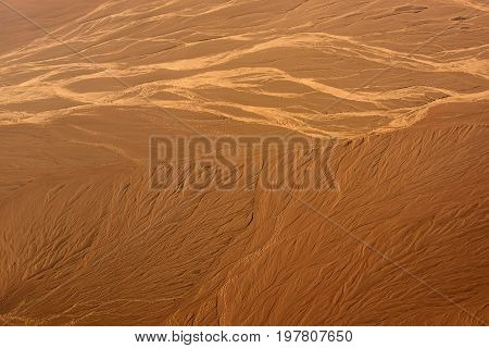 sand desert landscape aerial view with rugged brown terrains and barchans natural background