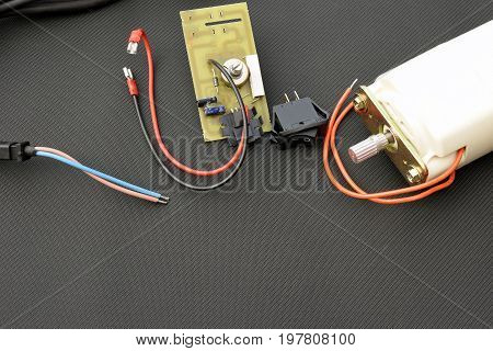 Parts for electric machine, motor, pcb, wires, potentiometer, switch. Horizontal image with copy space.