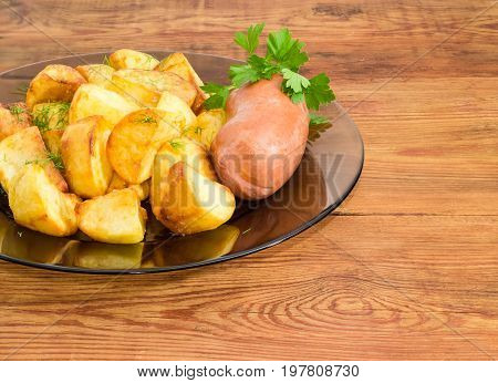 Fragment of the dark glass dish with fried potatoes sprinkled by chopped dill fried wieners and twig of parsley closeup on a surface of old wooden planks