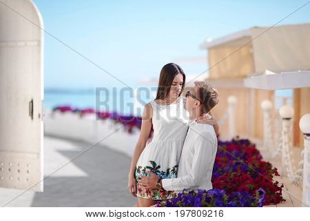 A cheerful and romantic couple relaxing on a sunny resort background. An adorable girlfriend and a smiling boyfriend. A Happy couple near pink and purple flowers on a sunny resort background.