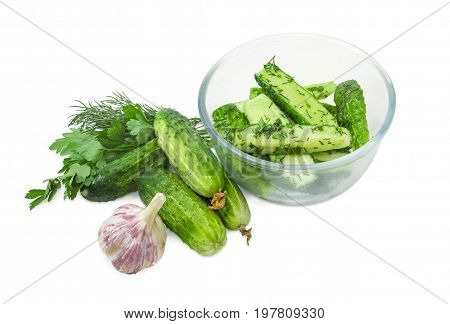 Lightly salted cucumbers in the glass bowl and several freshly picked out cucumbers parsley dill and garlic beside on a white background
