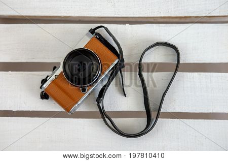 brown compact camera on white boards top view
