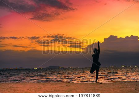 Young woman yoga exersice posting silhouette on the beach in summer