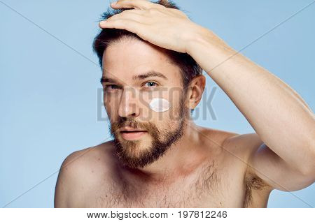 Man straightens hair, cream on cheek to care for face on blue background.