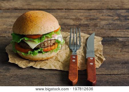 Homemade hamburger or sandwich on brown paper. Delicious sandwich hamburger with meat or pork ham cheese and fresh vegetable. Hamburger or sandwich is the popular fast food for brunch or lunch. Cheese burger ready to served.