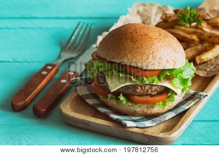 Homemade hamburger on plaid napkin with french fries. Delicious sandwich hamburger with meat or pork ham cheese and fresh vegetable. Hamburger or sandwich is the popular fast food for brunch or lunch.Cheese burger ready to served.