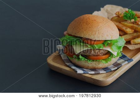 Homemade hamburger on plaid napkin with french fries. Delicious sandwich hamburger with meat or pork ham cheese and fresh vegetable. Hamburger or sandwich is the popular fast food for brunch or lunch. Cheese burger ready to served.