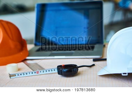 Helmets, laptop, roulette, builder's workplace, drawing paper.