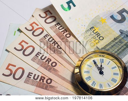 Euro banknotes like background and at the front are clocks that have five to twelve time. Highest time for action.