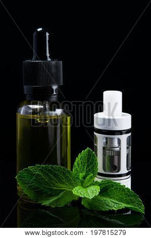 A white tank for an electronic cigarette stands next to a mint fluid