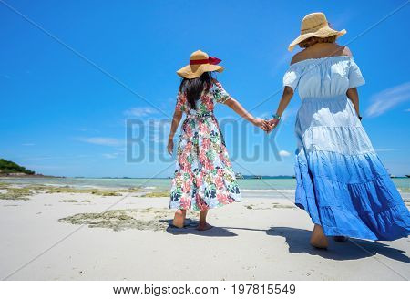 Young woman asian buddy in hawaii dress with hat walking together on sea beach summer fun and happy relax in vacation time
