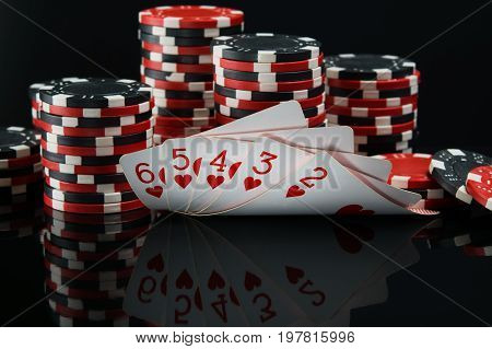 Straight flush on a mirror black background behind a big win