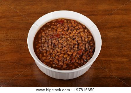 Fresh hot baked beans in a white casserole on a wood table