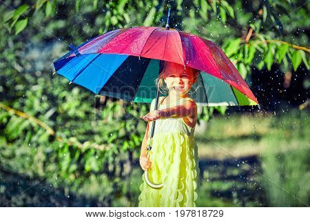 Happy child girl laughs and plays under summer rain with an umbrella