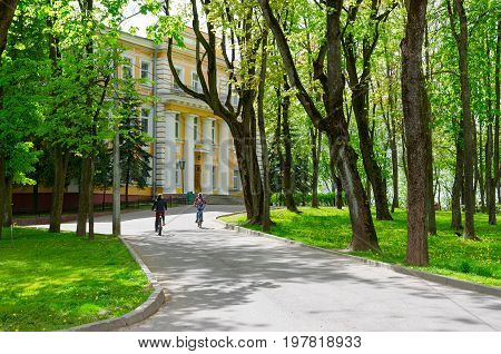 VITEBSK BELARUS - MAY 21 2-17: Square of heroes of Patriotic War of 1812 palace of governor of XVIII century. Unknown teenagers ride bicycles