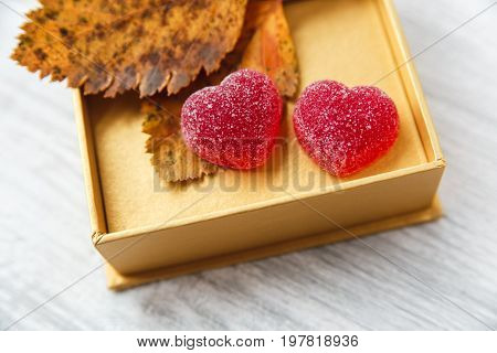 two red heart shape jelly candy in golden present box with leaves.white wooden table.