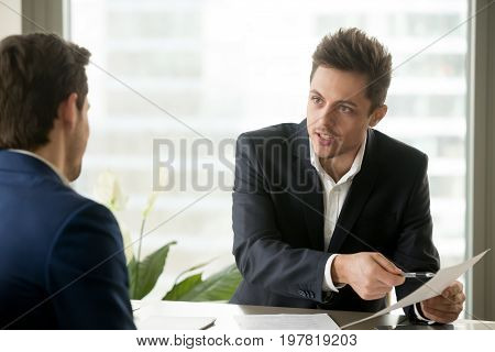 Financial adviser consulting businessman, holding paper, explaining contract terms or investment plan, bank worker helping client with document, salesman proposing good deal to customer, making offer