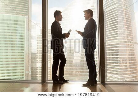 Two businessmen talking negotiating standing near large panoramic window with big city buildings, serious partners having business discussion in sunny office, discussing project ideas, side view