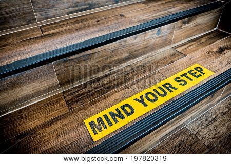 Mind your step sticker sign pasted on wooden stair. Warnings abstract or indoor architecture concept