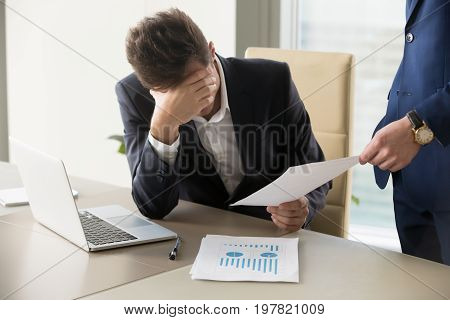 Sad manager getting notice of dismissal, sitting at workplace with laptop and financial documents, employee receiving letter with bad news, entrepreneur upset by commercial failure or firm bankruptcy poster