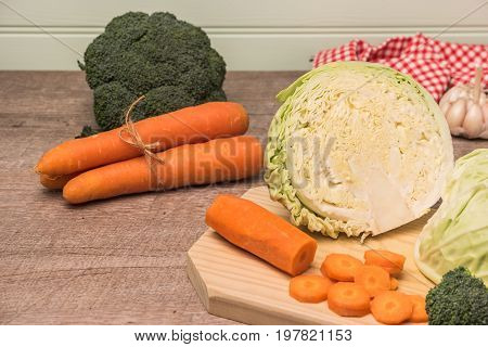Fresh vegetables from the garden carrots cabbage broccoli onion and garlic on a wooden table. Vegetables for preparing soup
