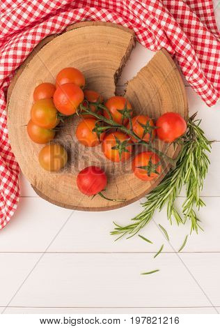 Organic cherry tomatoes with rosemary on rustic wooden table. Top view