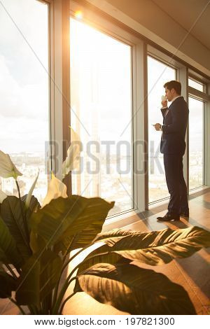 Successful businessman starting working day with cup of coffee, standing in modern sunny office interior, looking through full-length window at big city, having break, deep in thoughts, vertical view