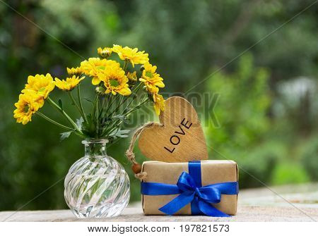 A bunch of yellow flowers a gift and a wooden heart. Romantic concept.