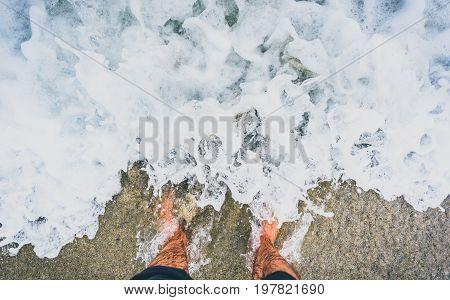 Person standing in ocean sea waves on sandy beach. Barefoot legs soaking in sea water. Man feet standing on sandy beach of Atlantic ocean in Galicia - Spain.