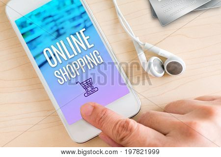 Hand touch smart phone and ear phone with Online shopping word on wood table Internet marketing concept